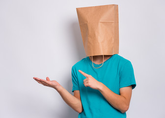 Fototapete - Teen boy with paper bag over head pointing finger away at copyspace, on gray background. Teenager cover head with shopping bag pointing finger at something. Child pulling paper bag over head