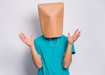 Fototapete - Portrait of surprised teen boy with paper bag over head raised hands on gray background. Happy child posing at studio.