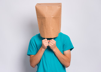 Fototapete - Portrait of teen boy with paper bag over head. Teenager cover head with bag holding hand near face posing in studio. Child pulling paper bag over head.