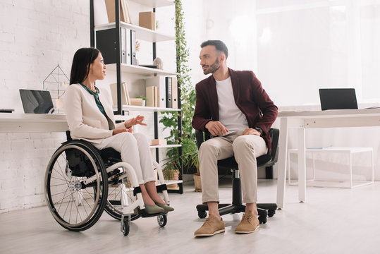 disabled businesswoman in wheelchair gesturing while talking to business partner in office