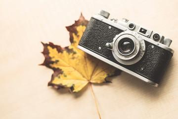 Old camera lies on autumn maple sheet