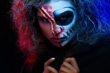 Close up of girl with halloween makeup wearing black cape