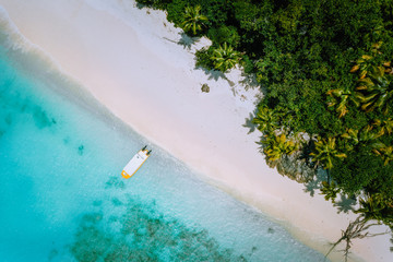 Top down aerial view of exotic tropical sandy beach with blue lagoon, palm trees and linely boat moored