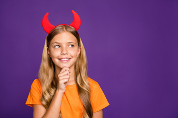 Photo of pretty little lady headband horns on head looking empty space thinking over evil trick on helloween party wear orange t- shirt isolated purple color background