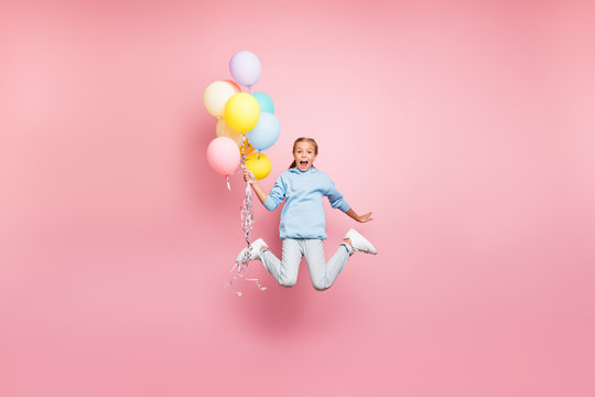 Full length body size photo of cheerfu positive cute nice screaming funny comic girl holding balloons with hands shouting flying jumping in blue sweatshirt sweater hoodie jeans denim isolated pastel