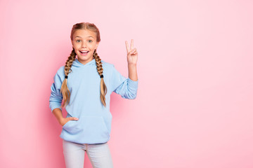 Hi you. What's up. Photo of pretty small lady raising hand showing v-sign symbol greets school friends wear casual blue pullover isolated pastel pink color background