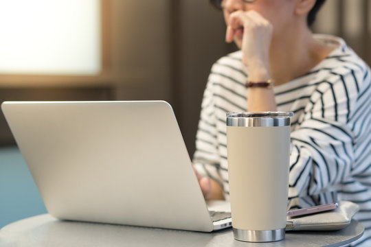 Smart looking woman use laptop computer to work from home due to Covid-19 pandemic, city lockdown and social distancing with her drink in a reusable stainless steel tumbler mug aside.