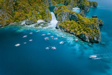 Aerial view of amazing Mililoc Island. Tourist boats near big Lagoon. El Nido, Palawan, Philippines. Surreal karst limestone rock formation