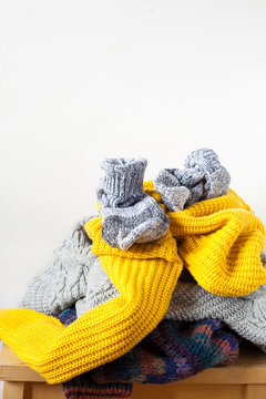 Pile colorful knitted wool clothes or sweaters on wooden table and white wall indoor close-up with copy space.Kinfolk minimal style.Donation and household concept