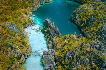Aerial drone view of a beautiful tropical Big Lagoon at Miniloc Island, El Nido, Philippines. Tourist kayaking surrounded by jagged limestone cliffs. Bacuit, Palawan