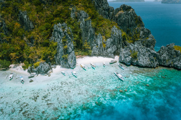 El Nido, Palawan, Philippines. Aerial view of tropical Island with tourist boats moored at white sandy beach. Old coral reef in front of jugged karst limestone mountain cliffs