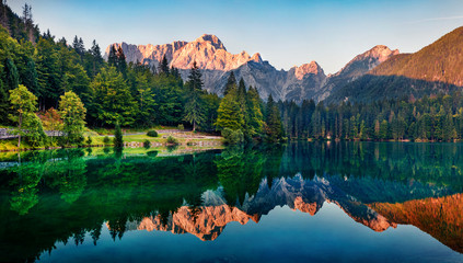 Poster Mountains Calm morning view of Fusine lake. Colorful summer sunrise in Julian Alps with Mangart peak on background, Province of Udine, Italy, Europe. Beauty of nature concept background.