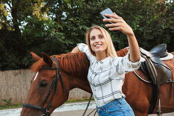 Beautiful smiling young blonde woman petting a horse at the stable