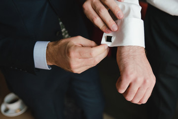 Wedding fashion for men. Closeup of caucasian man putting the cufflinks on the groom's shirt.
