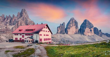 Impressive summer sunset with Paternkofel and Tre Cime Di Lavaredo mpountain peaks. Fantastic summer scene of rifugio Locatelli in Dolomiti Alps , South Tyrol, Italy, Europe.