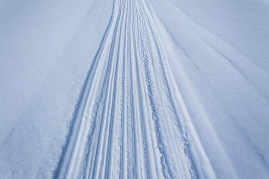 Traces of skis and sleds in the snow. Road on white snow