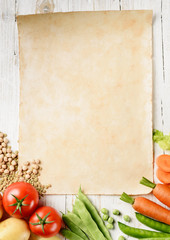 old paper sheet with veggies on white table, top view