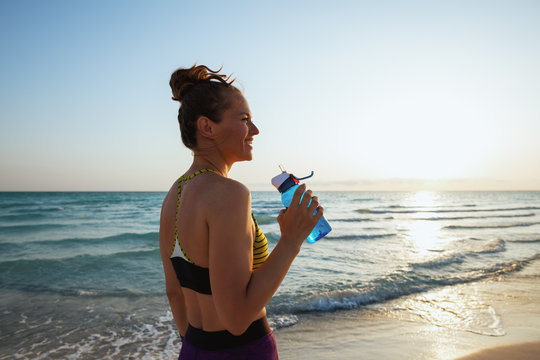 young woman with bottle of water on ocean coast at sunset