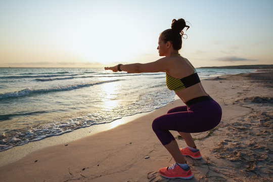 healthy woman on seashore in evening doing squats