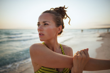 fitness woman on seacoast in evening stretching