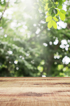 Wooden table and blurred green leaves nature bokeh background.