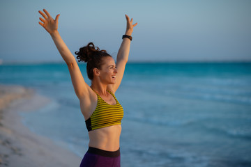 healthy sports woman on beach at sunset pointing at something