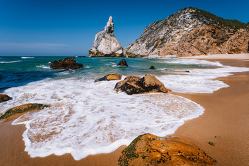 Portugal Ursa Beach at atlantic ocean coast. Foamy wave at sandy beach with surreal jugged rock in coastline picturesque landscape background
