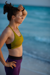 active woman in sport style clothes on ocean shore at sunset