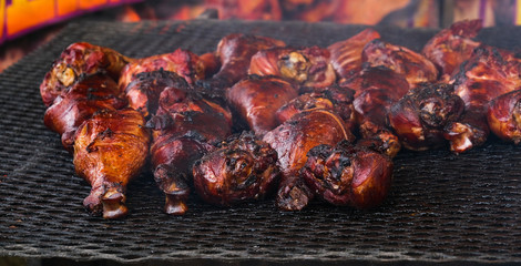 Many Smokey Turkey Legs on a Grill at a County Fair