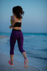 healthy sports woman on beach in evening jogging