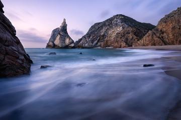 Epic Ursa Beach, Sintra, Portugal. Beach with waves and jugged rock peak in evening soft sunset light. Atlantic Ocean coast landscape