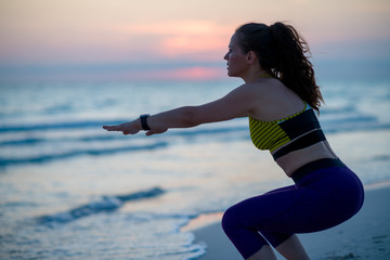 young sports woman on seashore in evening doing squats