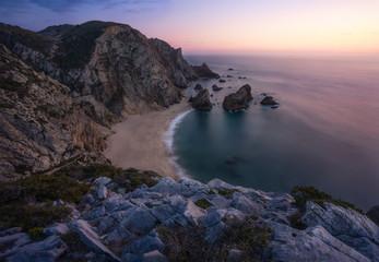 Sunset over a hidden surreal Praia Da Ursa Beach near Cabo Da Roca on Atlantic coast, Portugal, Europe