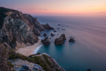 Sunset over a hidden surreal Praia Da Ursa Beach. Cabo Da Roca with light-house in background. Atlantic coast, Portugal, Europe