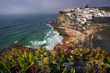 Dreamy view of the picturesque village Azenhas do Mar ins sunset light with chalk houses on the edge of a cliff and beach below. Sintra Landmark, Portugal, Europe