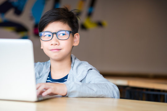 Smart looking Asian preteen boy with eye blue light blocking glasses rolling eyes smiling happily, using computer laptop to study online lessons. Online learning and self study concept.