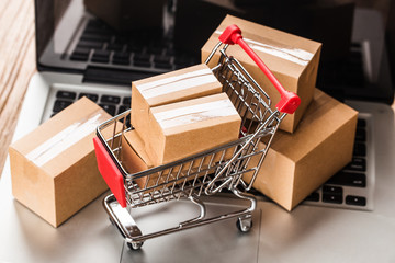 shopping online at home concept.Cartons in a shopping cart on a laptop keyboard