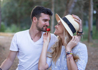 Happy young couple eating strawberry in nature