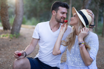 Young woman in hat feeding man with strawberry in nature