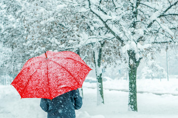 Woman under red umbrella walking in winter snow