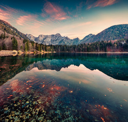 Great morning view of Fusine lake. Colorful autumn sunrise in Julian Alps with Mangart peak on background, Province of Udine, Italy, Europe. Beauty of nature concept background.