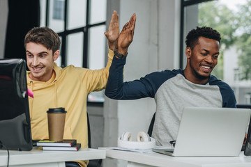 happy multicultural programmers giving high five while working in office together
