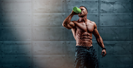 Nutritional Supplement. Muscular Men Drinks Protein, Energy Drink After Workout