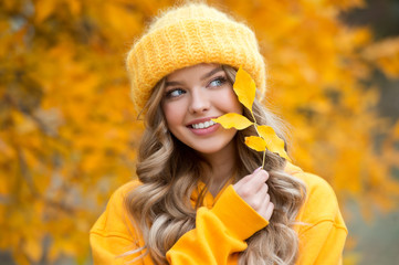 Beautiful girl walking outdoors in autumn. Smiling girl collects yellow leaves in autumn. Young...