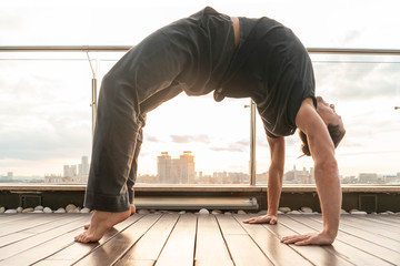 Attractive athletic man practicing yoga in business center with beautiful view on a city from skyscraper.