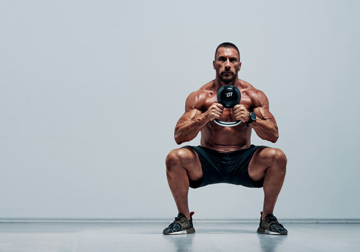 Handsome Muscular , Cross Training Athlete Doing Squats With Kettlebell