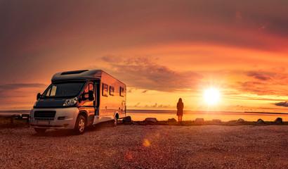 Glückliches Paar mit Wohnmobil am Strand