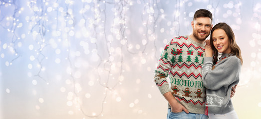 christmas, people and holidays concept - portrait of happy couple at ugly sweater party over festive lights background