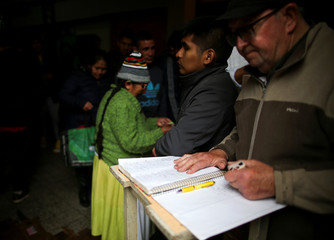 A man looks at a list of people assisting at a soup kitchen in Buenos Aires,
