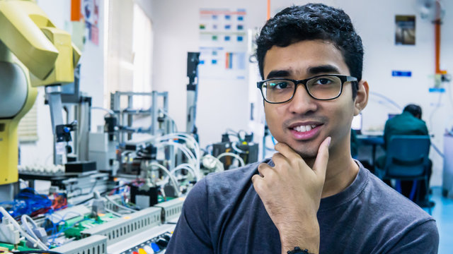 A young Malay engineering student with spectacles working in the lab and thinking by holding chin.